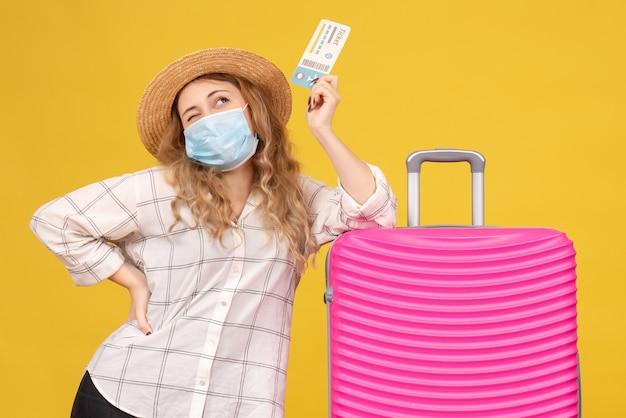Bovenaanzicht van denkende jonge dame die masker draagt met kaartje en in de buurt van haar roze tas staat