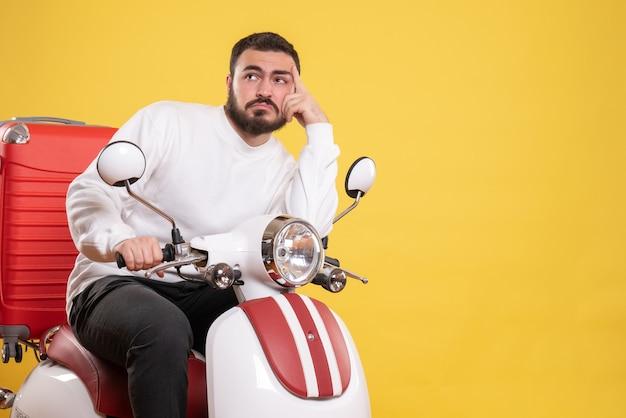 Bovenaanzicht van denkende jonge kerel zittend op motorfiets met koffer erop op geel