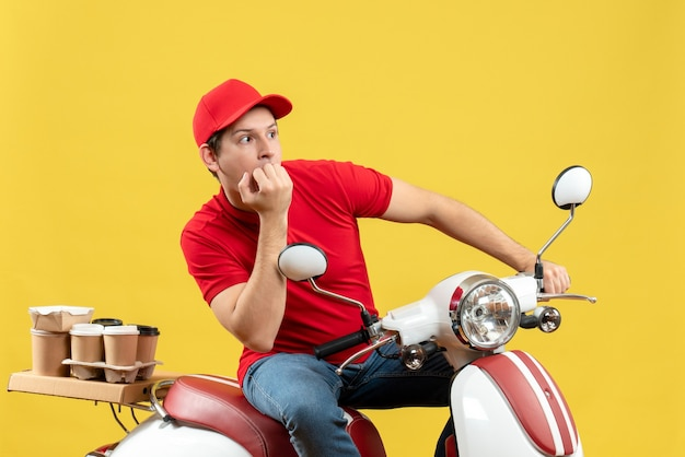 Bovenaanzicht van denkende jonge volwassene die rode blouse en hoed draagt die bestellingen op gele muur levert