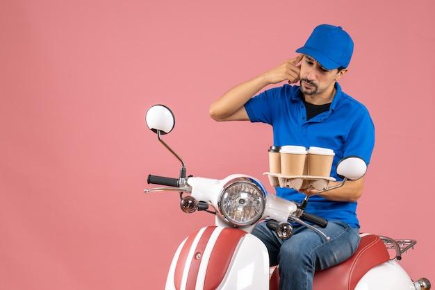 Bovenaanzicht van denkende koeriersman met hoed zittend op scooter op pastel perzik