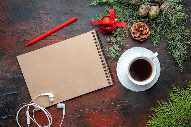 Bovenaanzicht van dennentakken een kopje zwarte thee decoratie accessoires witte hoofdtelefoon en cadeau naast notebook met pen op donkere achtergrond