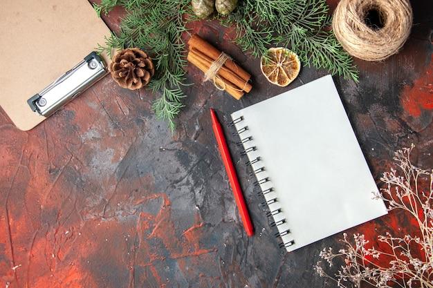 Bovenaanzicht van dennentakken en gesloten spiraal notebook kaneel limoenen conifer kegel een bal van touw op rode achtergrond