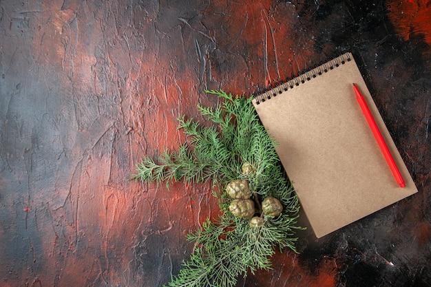 Bovenaanzicht van dennentakken en gesloten spiraalvormig notitieboekje met pen op donkere achtergrond