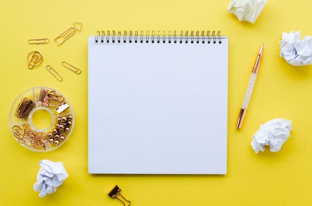 Bovenaanzicht van desktop met notebook en paperclips