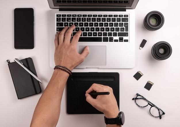 Bovenaanzicht van desktop voor fotograaf of ontwerper, met computer, tafel, koffie, notebook, mobiel, geheugenkaarten