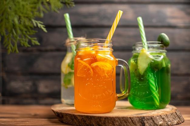 Bovenaanzicht van detox water en vers sap in flessen met buizen aan de linkerkant op bruin houten achtergrond