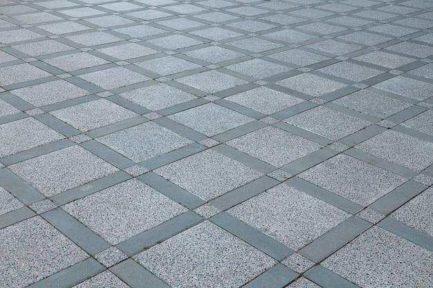 Bovenaanzicht van diagonale grijze ruitvormige vierkante bestrating van verschillende grootte