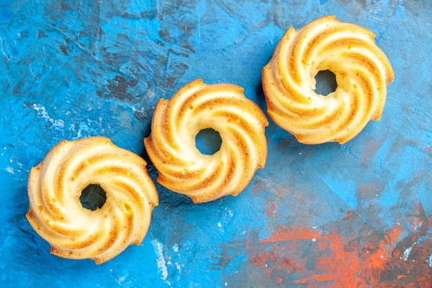 Bovenaanzicht van diagonale rij koekjes op blauwe ondergrond