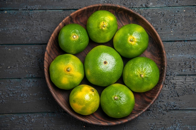Bovenaanzicht van dichtbij acht limoenen in een kom acht limoenen in een kom in het midden van de grijze tafel