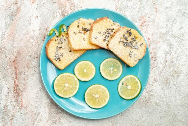 Bovenaanzicht van dichtbij brood en citroen gesneden citroen en wit brood in het bord op tafel