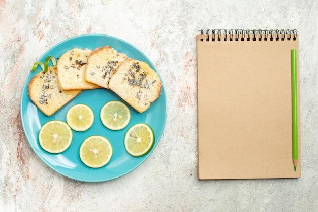 Bovenaanzicht van dichtbij brood en citroen gesneden citrusvruchten en wit brood in de plaat naast het crèmekleurige notitieboekje en potlood