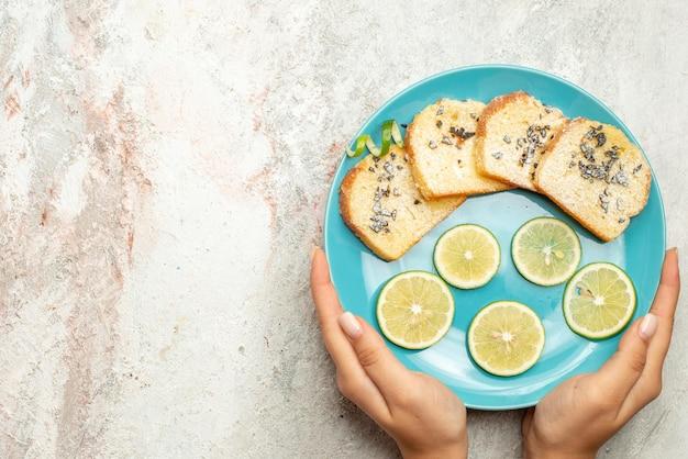 Bovenaanzicht van dichtbij brood en citroenblauw bord brood en gesneden citroen in de hand op de witte tafel