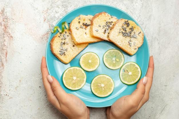 Bovenaanzicht van dichtbij brood en citroenblauw bord met gesneden citroen en wit brood in de hand