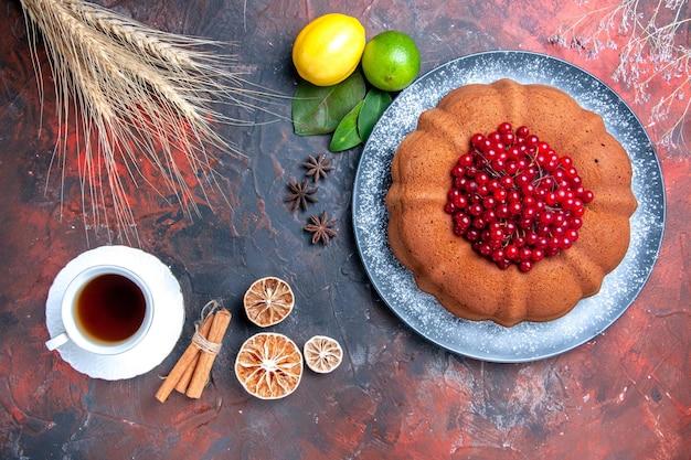 Bovenaanzicht van dichtbij cake citroenen kaneel een kopje thee steranijs cake met rode aalbessen