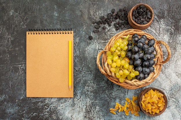 Bovenaanzicht van dichtbij druivenmand met druiven tussen kommen met gedroogde vruchten crème notitieboekje potlood