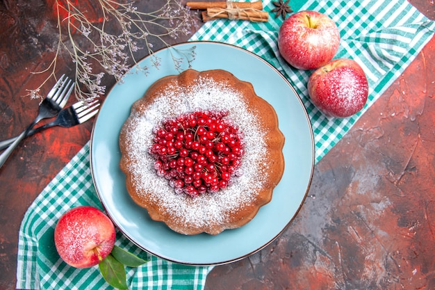 Bovenaanzicht van dichtbij een cake appels een cake met rode aalbessen op de tafellaken vorken