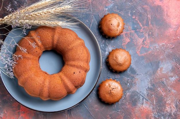 Bovenaanzicht van dichtbij een cake de smakelijke cake en drie cupcakes tarweoren boomtakken