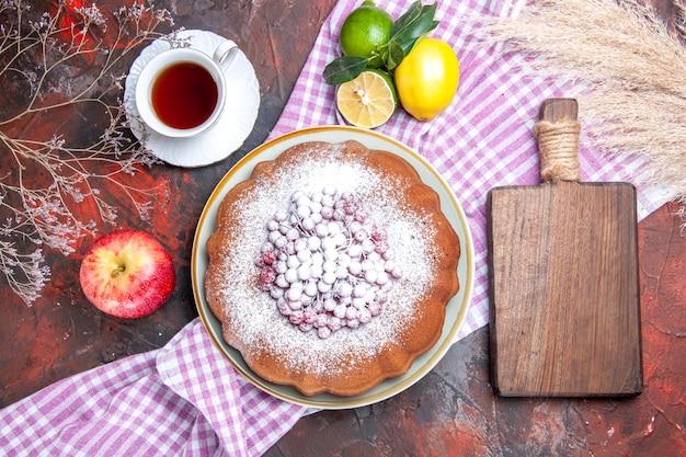 Bovenaanzicht van dichtbij een cake een cake een kopje thee citrusvruchten de snijplank tarweoren