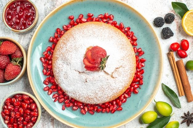 Bovenaanzicht van dichtbij een cake een cake met aardbeien kaneelstokjes kommen met bessen limoenen steranijs