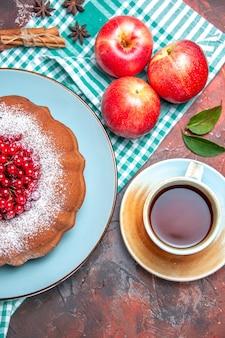 Bovenaanzicht van dichtbij een cake een cake met bessen appels een kopje thee kaneelstokjes steranijs