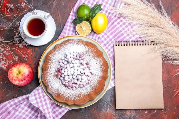 Bovenaanzicht van dichtbij een cake een cake met bessen een kopje thee citrusvruchten notitieboekje tarweoren