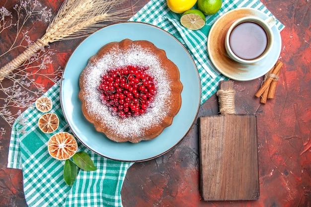 Bovenaanzicht van dichtbij een cake een kopje thee kaneelcake limoenen op het tafelkleed de snijplank