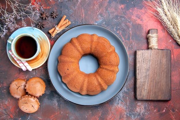 Bovenaanzicht van dichtbij een cake een kopje thee snoepjes een cake cupcakes kaneel en de snijplank