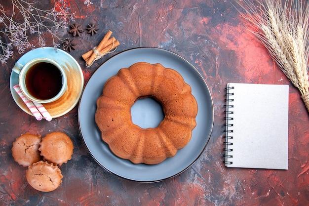 Bovenaanzicht van dichtbij een cake een kopje thee snoepjes een cake cupcakes kaneel en notitieboekje