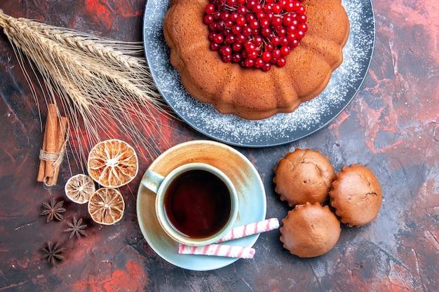 Bovenaanzicht van dichtbij een kopje thee een cake met rode bessen snoepjes cupcakes een kopje thee kaneel