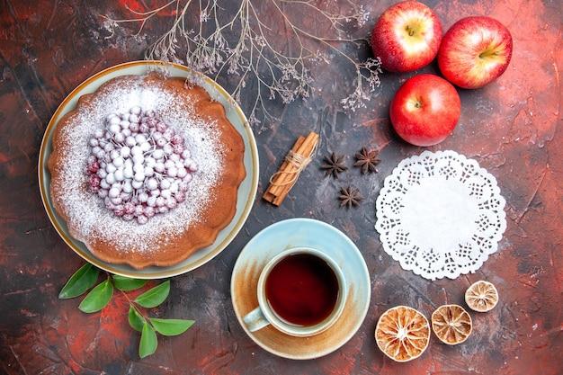 Bovenaanzicht van dichtbij een kopje thee een kopje thee een cake steranijs appels takken kanten kleedje