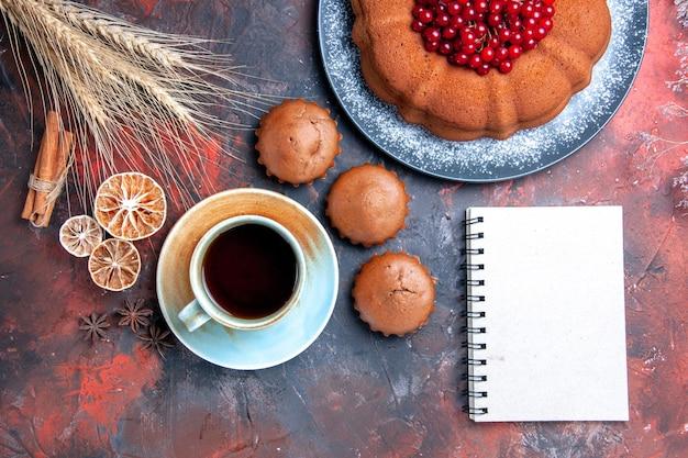 Bovenaanzicht van dichtbij een kopje thee een smakelijke cake cupcakes een kopje thee kaneel notitieboekje
