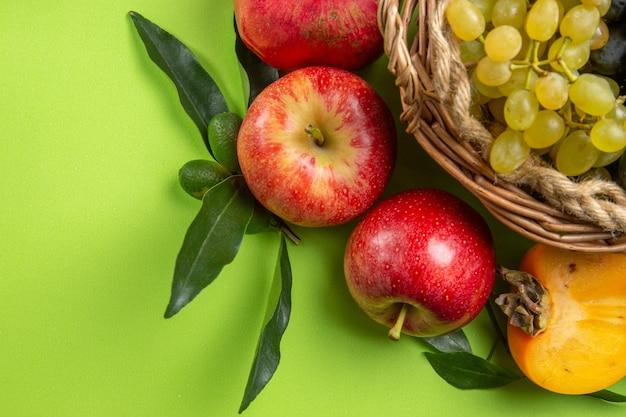 Bovenaanzicht van dichtbij fruit appels granaatappels persimmon druiven en bladeren
