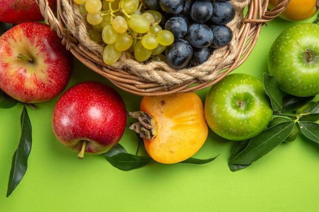 Bovenaanzicht van dichtbij fruit appels mand met druiventrossen kaki bladeren