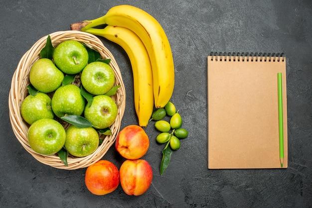 Bovenaanzicht van dichtbij fruit bananen limoenen appels in de mand nectarines naast het notitieboekje potlood