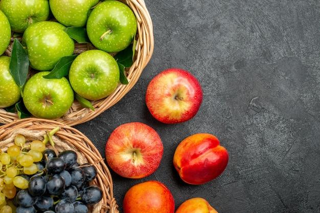 Bovenaanzicht van dichtbij fruit de smakelijke appels en druiventrossen in de mand en nectarines