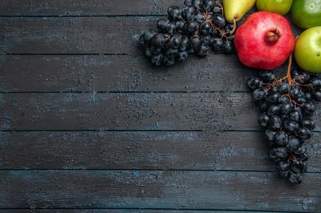 Bovenaanzicht van dichtbij fruit granaatappel appel peer limoenen en druiven aan de rechterkant van de donkere tafel