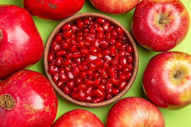 Bovenaanzicht van dichtbij fruit granaatappels appels bruine kom met zaden van granaatappel