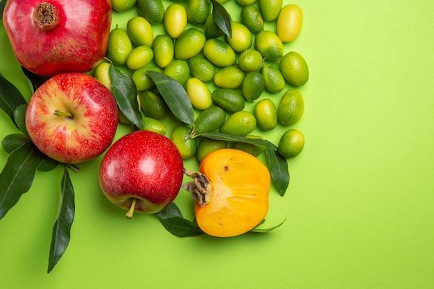 Bovenaanzicht van dichtbij fruit granaatappels appels groene citrusvruchten kaki op tafel