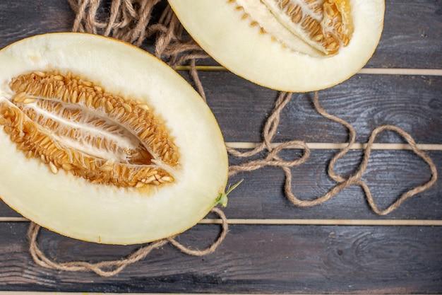 Bovenaanzicht van dichtbij gesneden meloen half gesneden zoet fruit op het bruine rustieke bureau