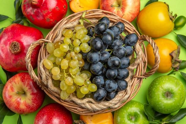 Bovenaanzicht van dichtbij kleurrijk fruit granaatappel appels kaki bladeren mand met druiven