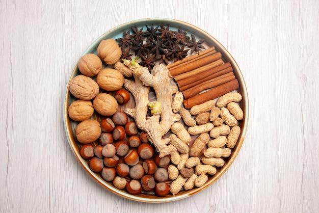 Bovenaanzicht van dichtbij noten bord walnoten hazelnoten kaneelstokjes pinda's en steranijs