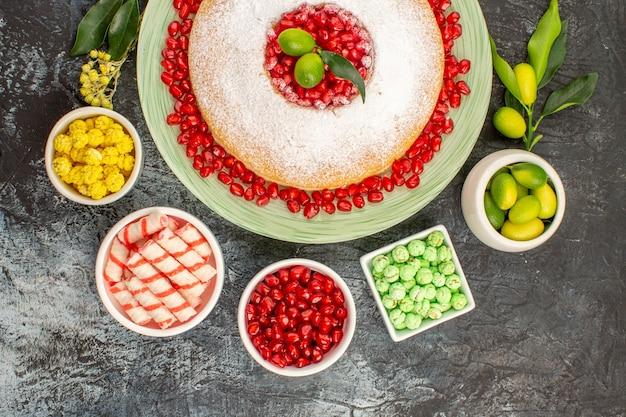 Bovenaanzicht van dichtbij snoepjes een smakelijke cake drie kommen limoenen snoepjes zaden van granaatappel