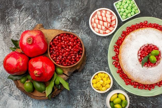 Bovenaanzicht van dichtbij snoepjes granaatappels op het bord een smakelijke taartkommen met snoep