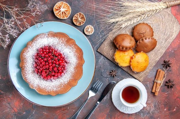 Bovenaanzicht van dichtbij taart cupcakes vier cupcakes een taart een kopje thee kaneel citroen mes vork