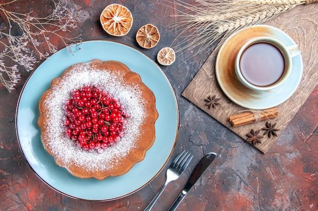 Bovenaanzicht van dichtbij taart een taart een kopje thee kaneel steranijs citroen mes vork