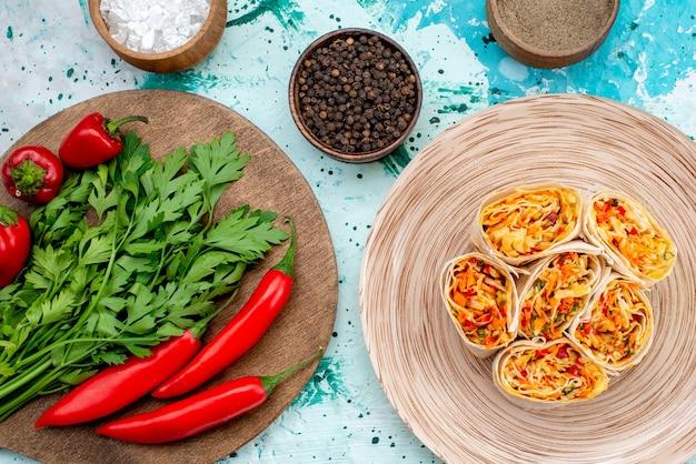 Bovenaanzicht van dichterbij gesneden groentebroodjes deeg met smakelijke vulling samen met greens en rode pittige paprika's op helderblauw bureau