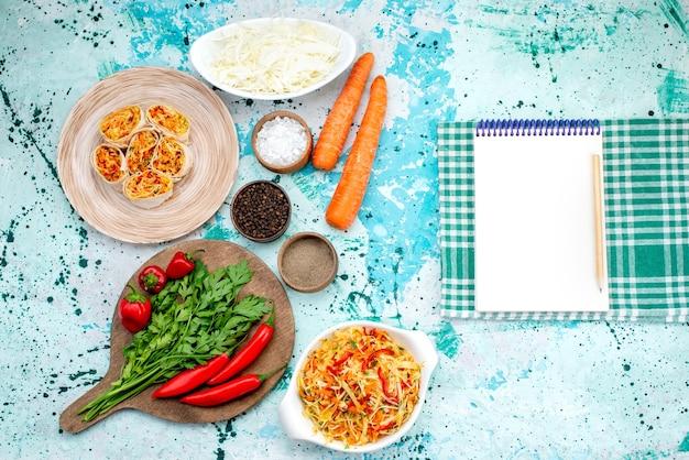 Bovenaanzicht van dichterbij gesneden groentebroodjes deeg met smakelijke vulling samen met groene blocnote en rode pittige paprika's op helderblauw bureau