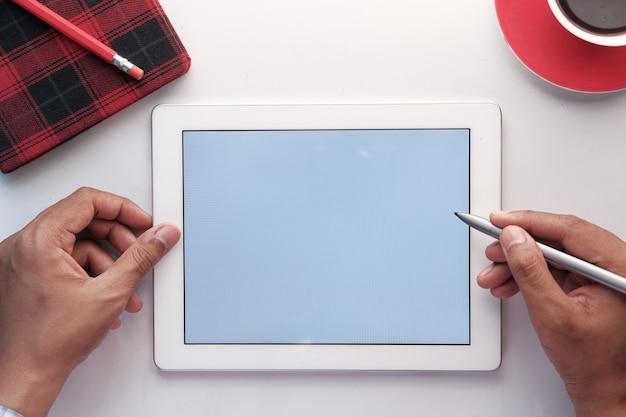 Bovenaanzicht van digitale tablet met kantoorleveranciers op tafel