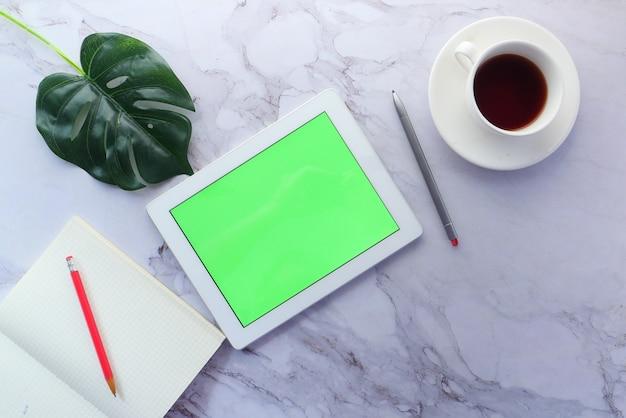 Bovenaanzicht van digitale tablet met kantoorleveranciers op tafel.
