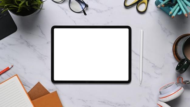 Bovenaanzicht van digitale tablet met wit scherm omgeven briefpapier, hoofdtelefoon en notitieboek op marmeren tafel.